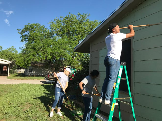 Goodfellow volunteers paint while Elia Juarez watches the progress at 1522 Wynne Ave. at the Neighborhood Painting Blitz on Saturday, April 27, 2019.
