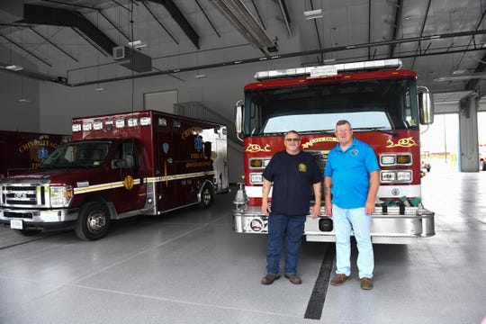 The new Chincoteague Volunteer Fire Department Chief Skibo Clark and Assistant Chief Harry Thornton pose for a photo as they have placed the fire truck in the new building for the first time on Wednesday, May 1, 2019.