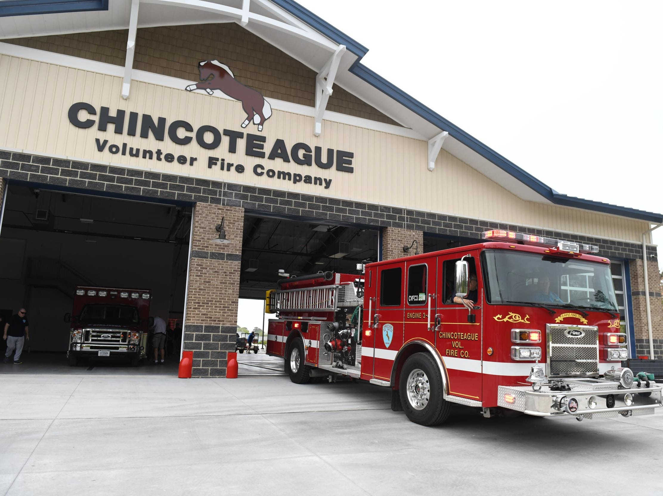 The new Chincoteague Volunteer Fire Department backs in the fire truck for the first time, as they start the process of moving into their new location at 5175 Chicken City Road at on Wednesday, May 1, 2019.