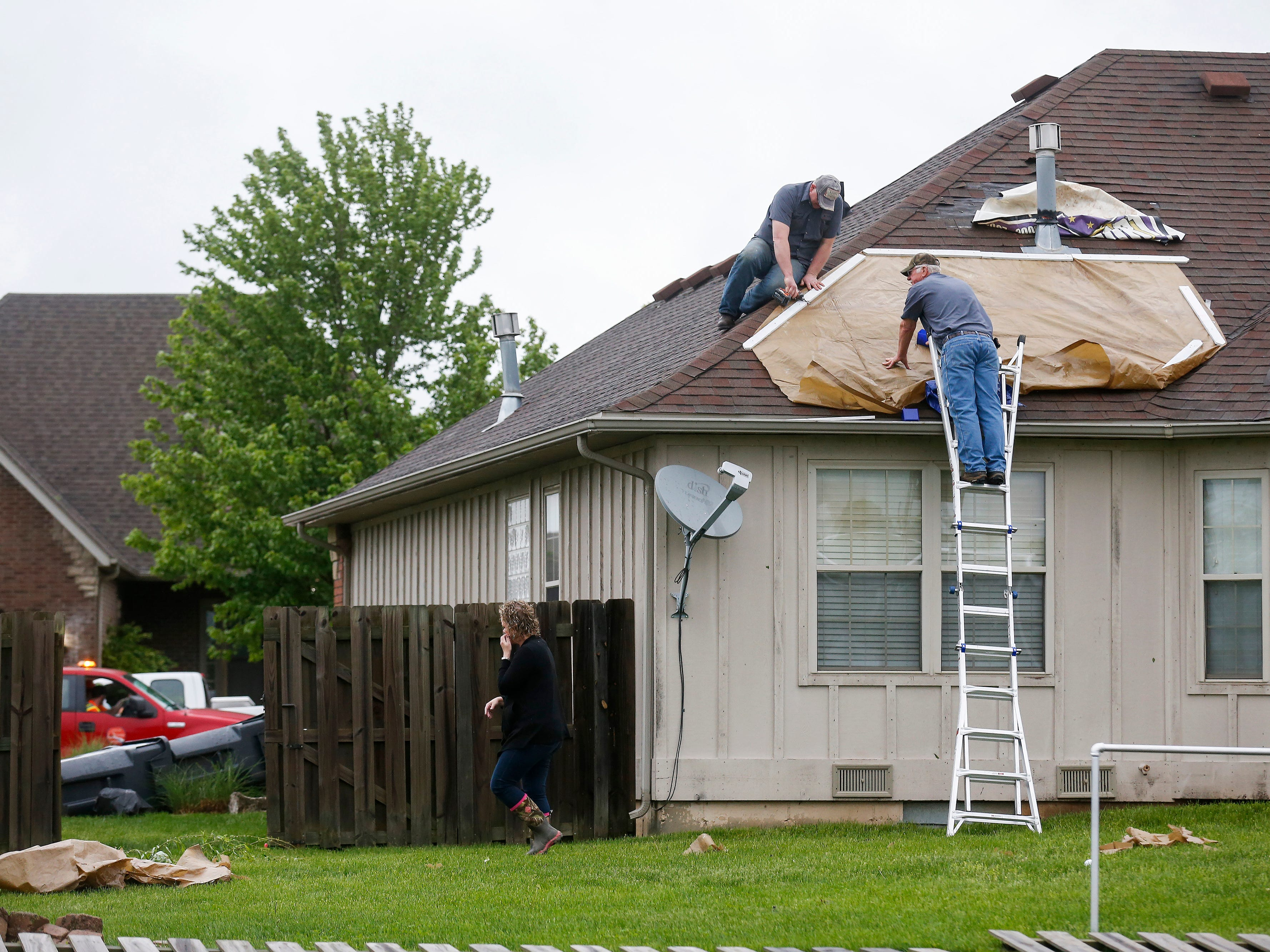 People put a tarp on a roof Wednesday in the Waterford neighborhood. A likely tornado moved through the Ozark Tuesday April 30, 2019 and caused extensive damage.