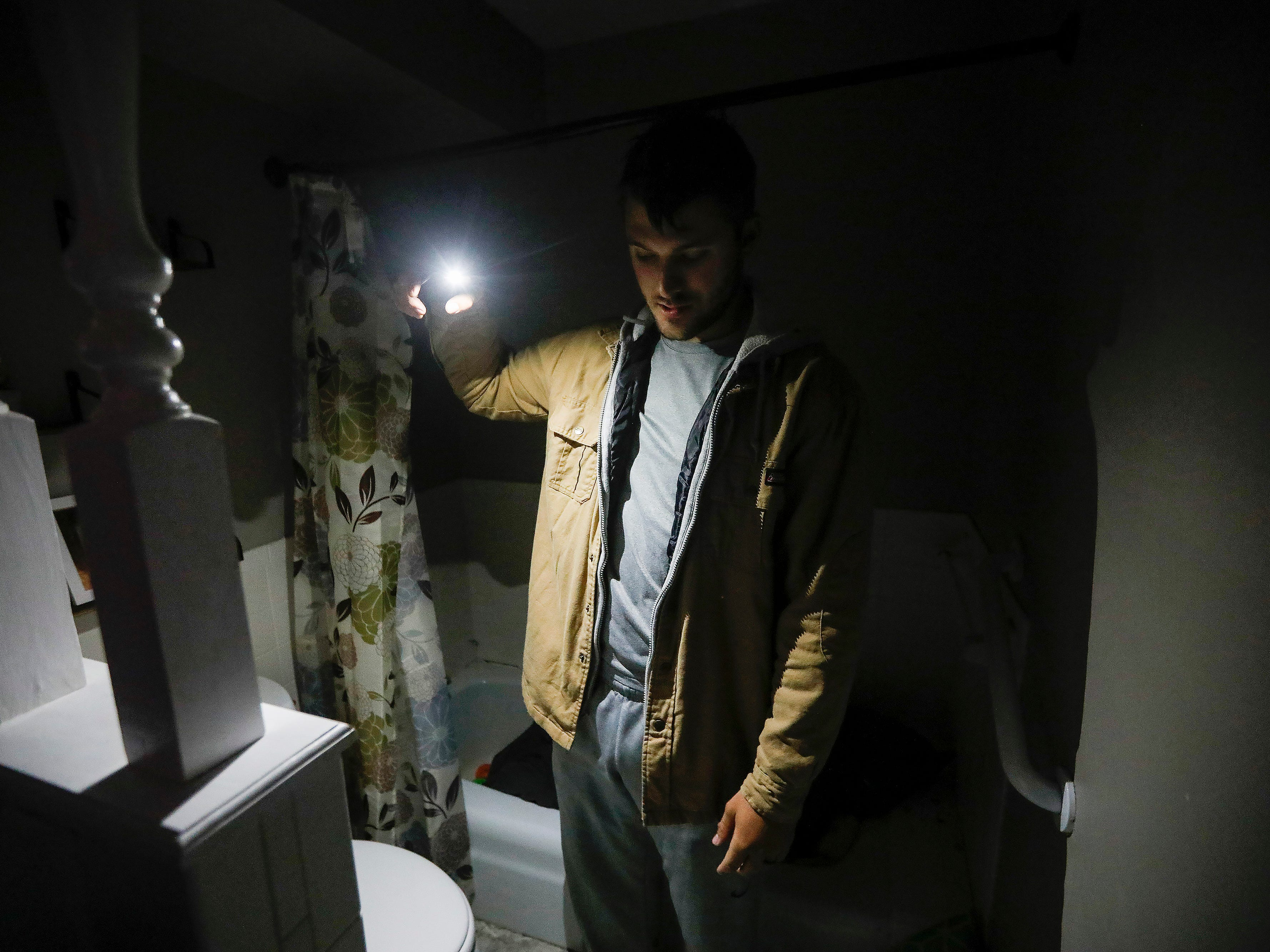 Denton Wilson uses a flashlight to illuminate the bathroom where he and his family took shelter during a likely tornado that hit Ozark on Tuesday, April 30, 2019.