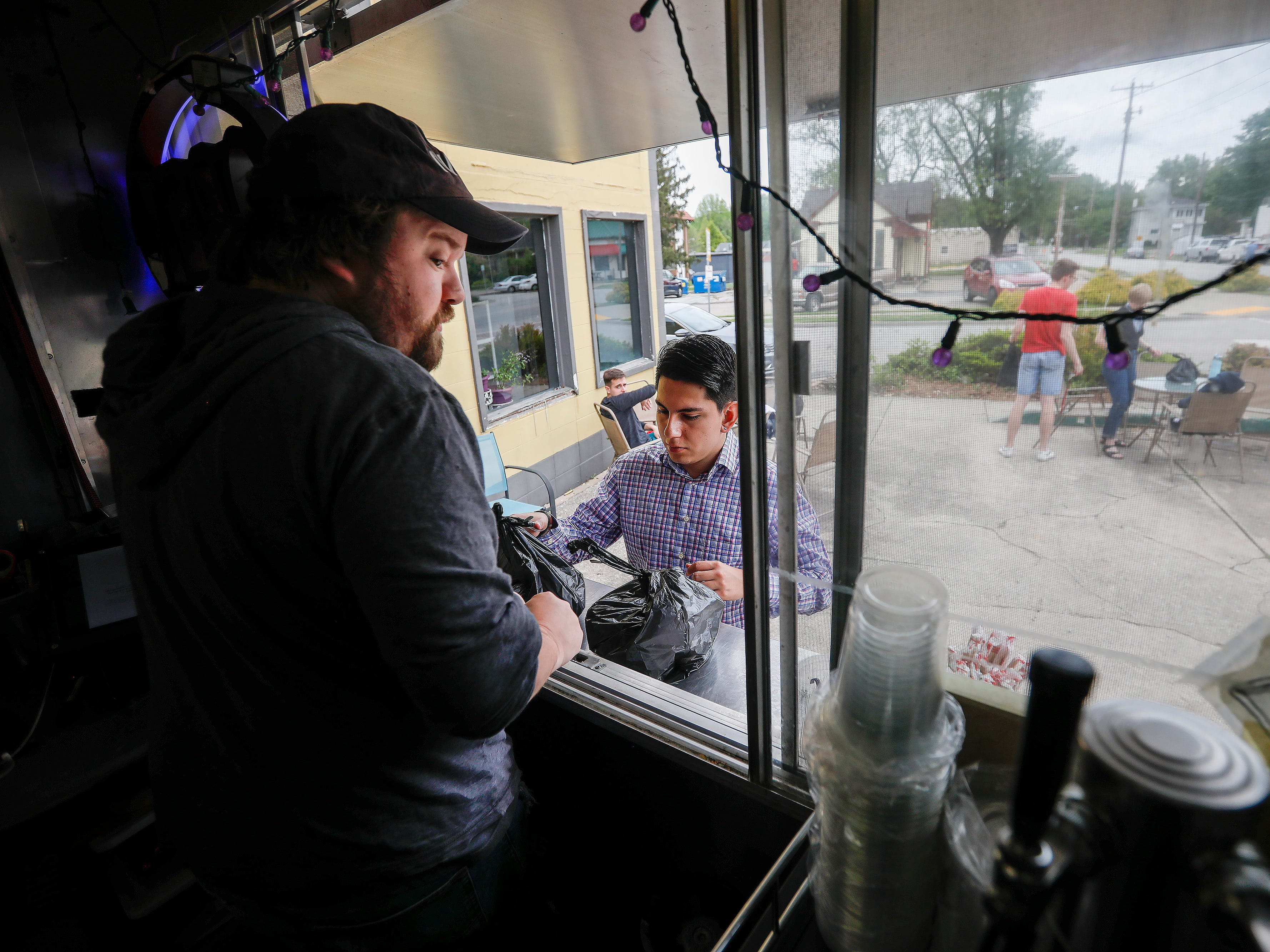Juan Molano, center, picks up his lunch from Jeremy Spinks at Skully's Food Truck at the corner of Cherry Street and Pickwick Avenue on Wednesday, May 1, 2019. Skully's will be moving inside into the former Josh Mitchell Art Gallery building.
