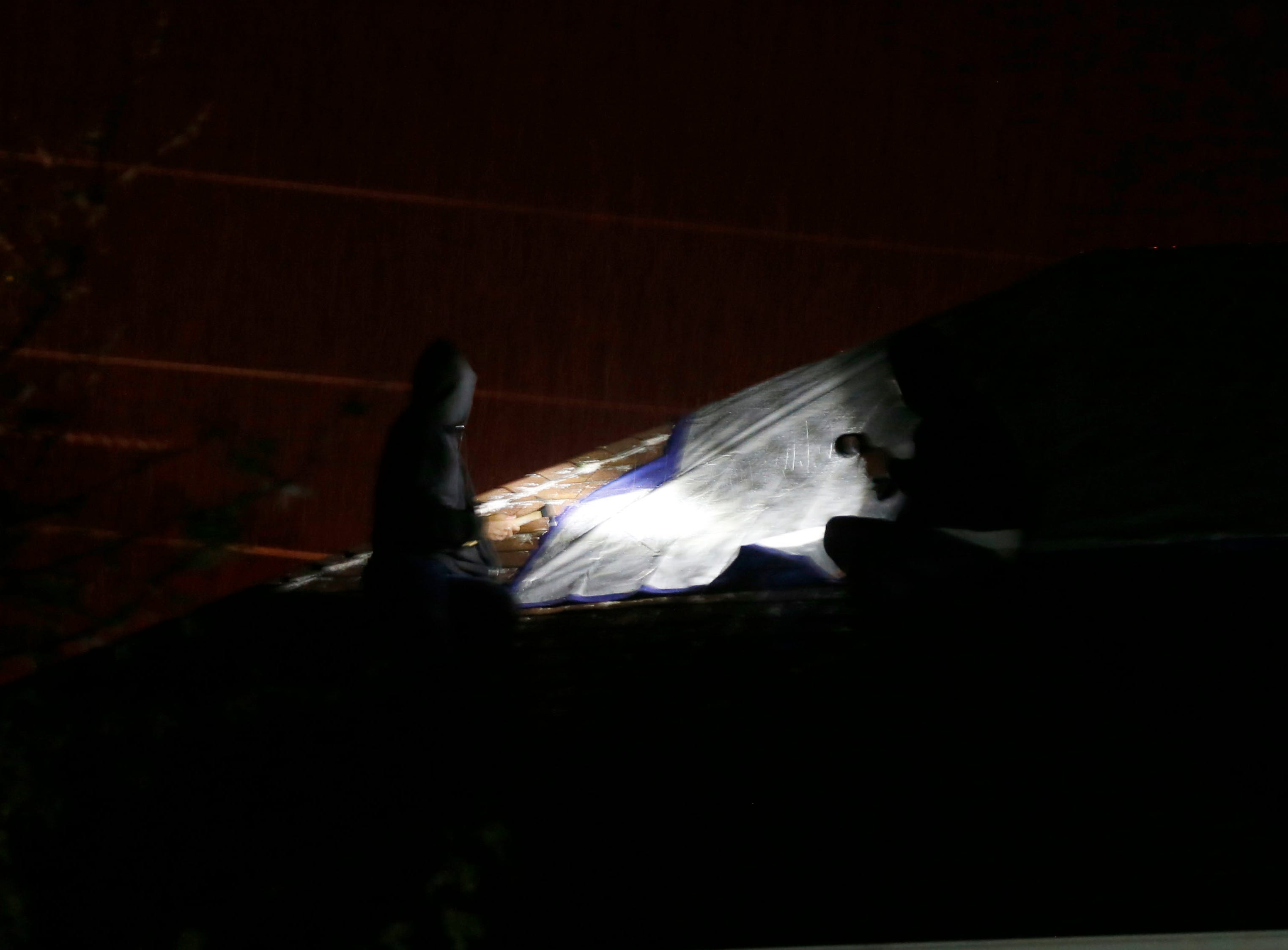 Residents work to put a tarp on his roof after what is believed to be a tornado damaged several houses in the Waterford neighborhood in Ozark on Tuesday, April 30, 2019.