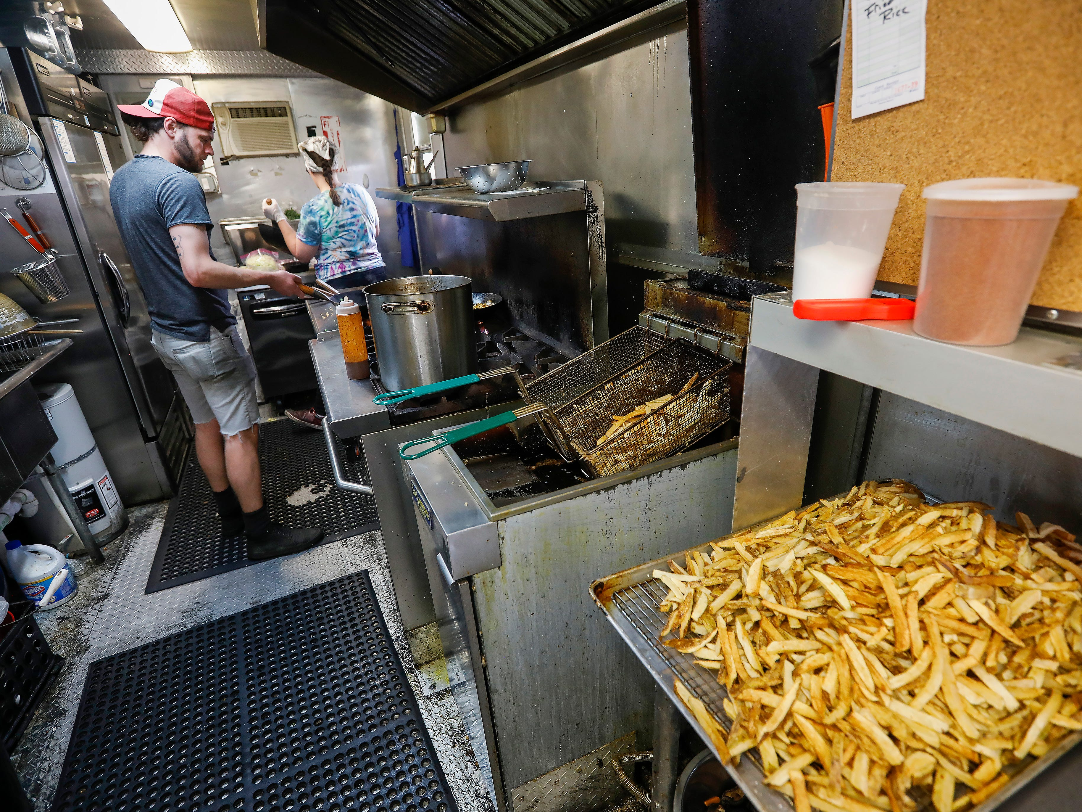 Joe and Lora Still work in the kitchen of Skully's Food Truck at the corner of Cherry Street and Pickwick Avenue on Wednesday, May 1, 2019. Skully's will be moving inside into the former Josh Mitchell Art Gallery building.