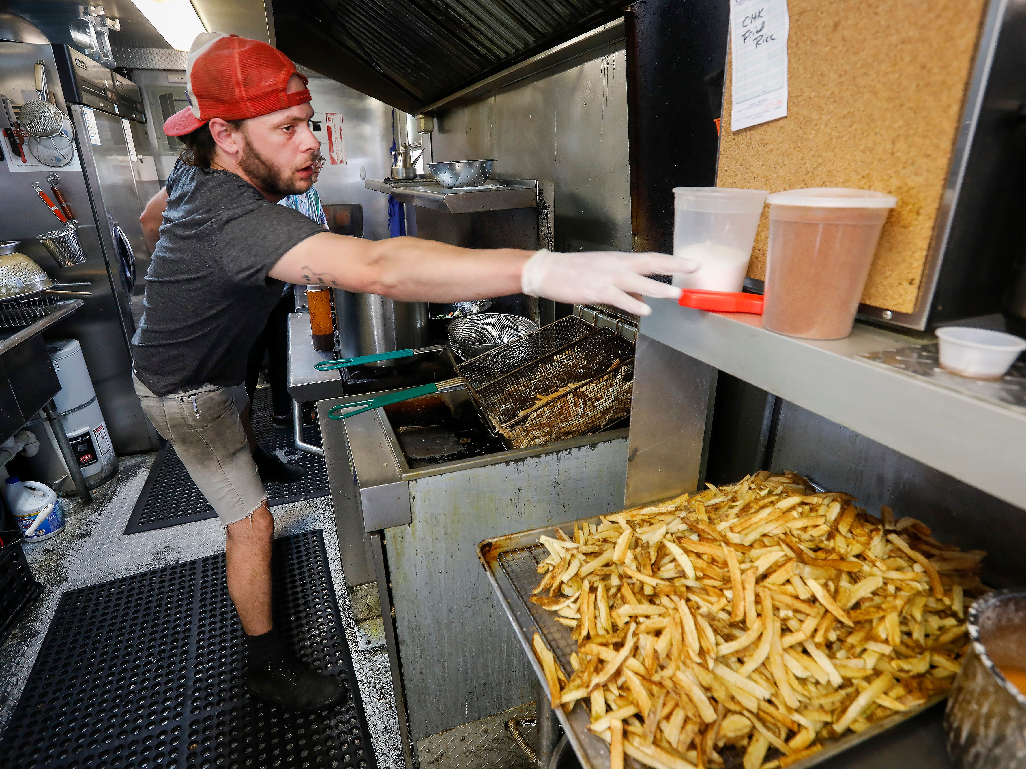 Joe Still reaches for a meat thermometer while working in the kitchen of Skully's Food Truck at the corner of Cherry Street and Pickwick Avenue on Wednesday, May 1, 2019. Skully's will be moving inside into the former Josh Mitchell Art Gallery building.