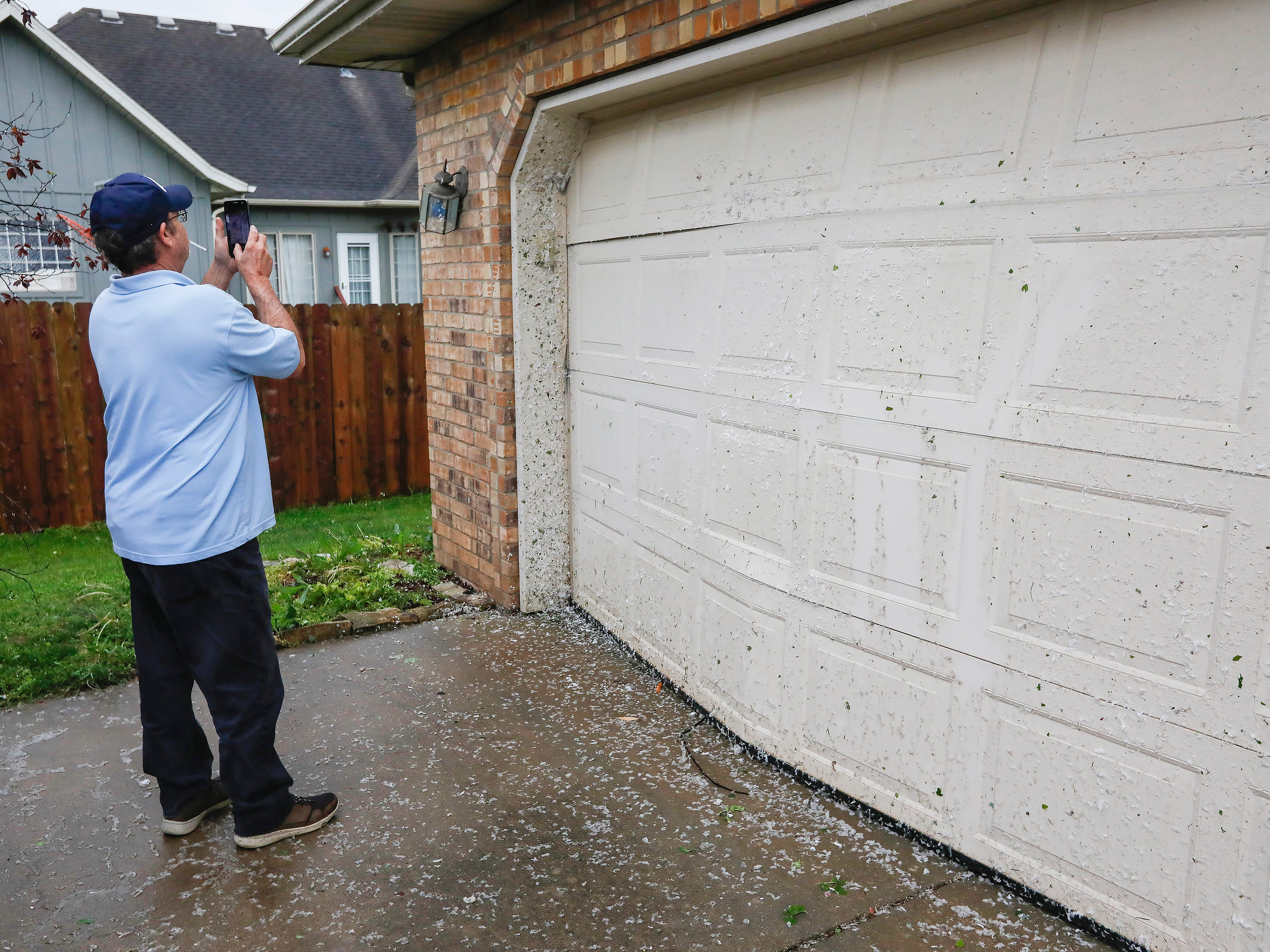 Steve Byard takes a photo of his garage Wednesday in the Waterford neighborhood that was damaged by a likely tornado that hit Ozark on Tuesday, April 30, 2019.