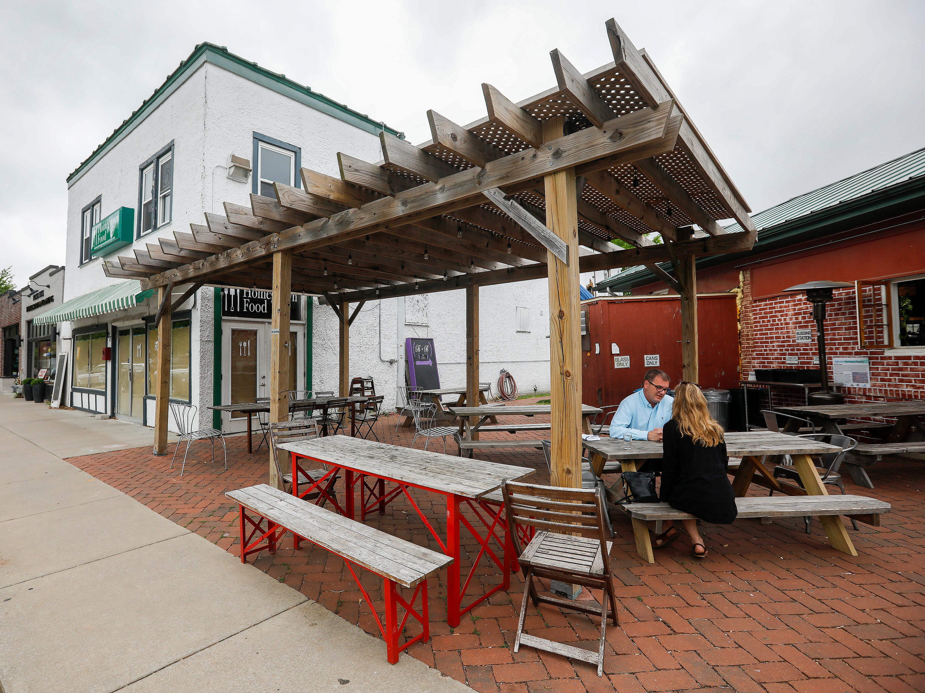 A couple sits outside of Cherry Picker Package x Fare and the former Homegrown Food in the Rountree neighborhood on Tuesday, April 30, 2019.