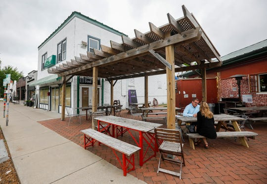A couple sits in the patio outside of Cherry Picker Package x Fare and the former Homegrown Food in the Rountree neighborhood on Tuesday, April 30, 2019.