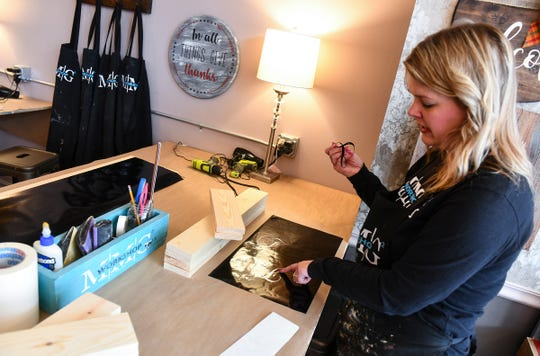 Jen Monroe demonstrates the process used to create custom signs Wednesday, May 1, at  MMG² Workshop in downtown St. Cloud.