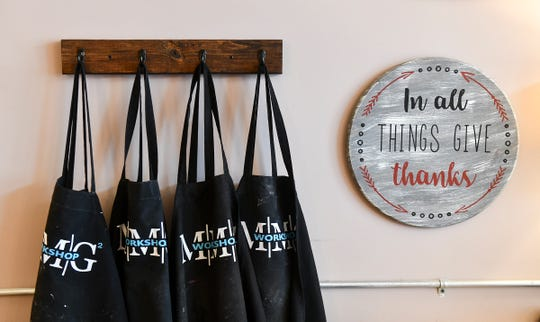 Aprons hang on the wall next to a custom sign Wednesday, May 1, at  MMG² Workshop in downtown St. Cloud.