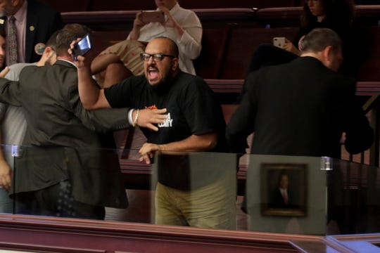 "While live streaming on Facebook, Carlos Naranjo is removed from the House of Representatives gallery by sergeants after entering the gallery with others and unfolding a banner reading: """"Your unjust laws won't break us we stand on the shoulders of giants"" and yelling in protest to a plethora of upcoming bills Wednesday, May 1, 2019."