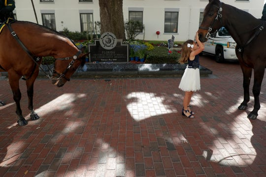 Emma Johnson, 7,  daughter of K9s United founder Debbie Johnson, shares a moment with Ditto, an Orange County Sheriff's Department mounted horse on the day Gov. Ron DeSantis signed a bill to create harsher penalties for criminals who harm law enforcement animals in the Capitol courtyard Wednesday, May 1, 2019.