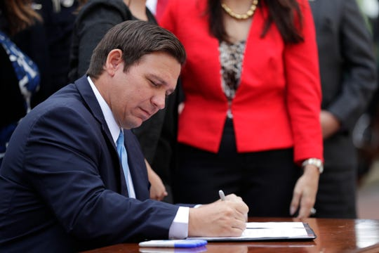 Gov. Ron DeSantis signs a bill that creates harsher penalties for criminals who harm law enforcement animals in the Capitol courtyard Wednesday, May 1, 2019.