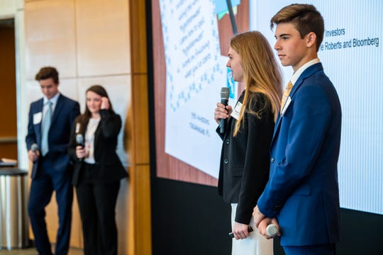 Madeleine Roberts, second from right, gives opening remarks about their investing philosophy to a room of fellow competitors and Wharton judges during the Knowledge@Wharton High School Investment Competition in March.