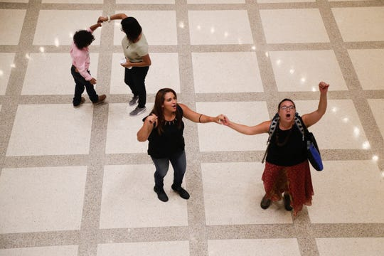 Karen Caudillo, a UCF student, dances with Isaac Diaz, 7, of Tampa while Flavia Franco and Eylin Garcia lead chants of about a hundred protestors in the Capitol rotunda after nearly a dozen were removed from the House of Representatives gallery Wednesday, May 1, 2019.