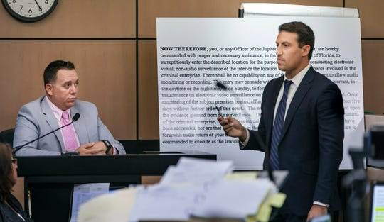 Alex Spiro, right, attorney for New England Patriots owner Robert Kraft, stands in front of a copy of a search warrant as he questions Jupiter Police Detective Andrew Sharp during a motion hearing in the Kraft prostitution solicitation case, Wednesday, May 1, 2019, in West Palm Beach. Kraft's attorneys argue that undercover surveillance videos allegedly showing their client paying for sex at a Jupiter day spa should be ruled inadmissible and the evidence thrown out.