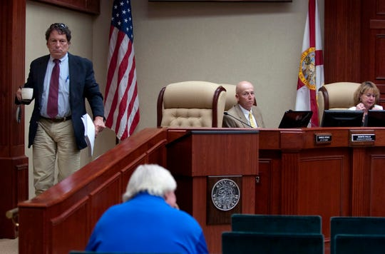 Vero Beach City Attorney Charles Vitunac, left, carries out his belongings after being voted out of his position by members of the Vero Beach City Council Feb. 1, 2011. Interim City Manager Monte Falls and City Clerk Tammy Bursick are seen on the dais.