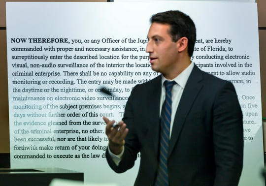 Alex Spiro, attorney for New England Patriots owner Robert Kraft, stands in front of a copy of a search warrant as he questions Jupiter Police Detective Andrew Sharp during a motion hearing in the Kraft prostitution solicitation case, Wednesday, May 1, 2019, in West Palm Beach. Kraft's attorneys argue that undercover surveillance videos allegedly showing their client paying for sex at a Jupiter day spa should be ruled inadmissible and the evidence thrown out.