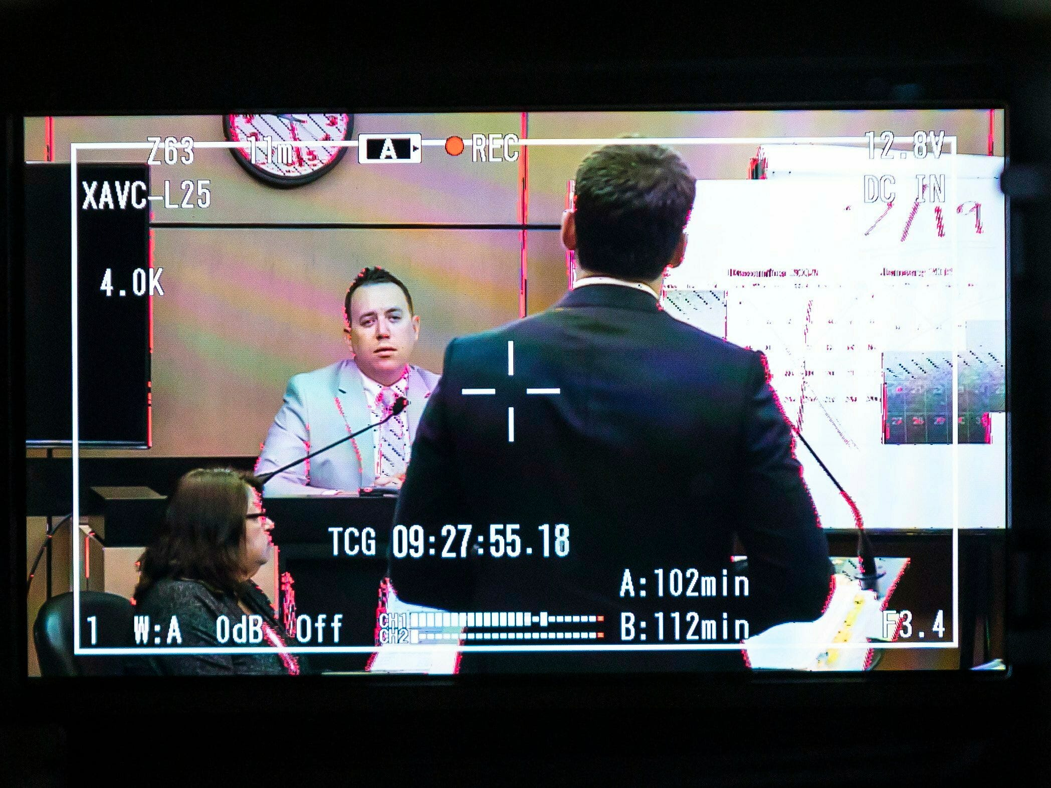 Jupiter Police Detective Andrew Sharp, displayed on a courtroom camera monitor, is questioned by Alex Spiro, right, attorney for New England Patriots owner Robert Kraft, during a motion hearing in the Kraft prostitution solicitation case, Wednesday, May 1, 2019, in West Palm Beach. Kraft's attorneys argue that undercover surveillance videos allegedly showing their client paying for sex at a Jupiter day spa should be ruled inadmissible and the evidence thrown out.