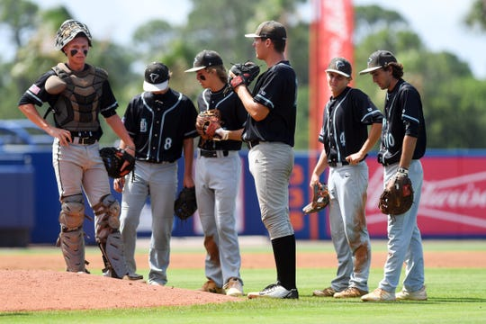 Jensen Beach catcher Caleb Pendleton (far left) stands with his teammates during a pitching change in a game against John Carroll Catholic on May 1, 2019 at Clover Park. Pendleton was expected to be one of the Treasure Coast's top draft picks before the draft was reduced to five rounds.
