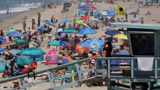 In this 2017 file photo, a lifeguard scans a crowded shoreline at Manhattan Beach. New population estimates show California's births fell by 18,000 last year, prompting the slowest recorded growth rate in the country's most populous state.
