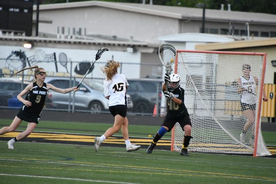 Newbury Park's Emma Ing attempts to shoot past Oak Park goalie Brooke La Torra on Tuesday night in the first round of the USL-Southern Section Northern Division girls lacrosse playoffs. Newbury Park won, 15-8.