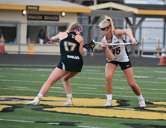 Oak Park's Riley deVarennes and Newbury Park's Erin Duffy ready for a draw on Tuesday night in the first round of the USL-Southern Section Northern Division girls lacrosse playoffs. Newbury Park won, 15-8.