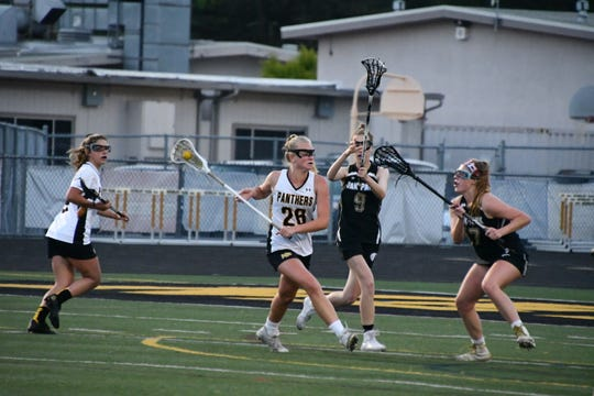 Newbury Park's Erin Duffy is defended by Oak Park's Erin Dotson and Riley deVarennes on Tuesday night in the first round of the USL-Southern Section Northern Division girls lacrosse playoffs. Newbury Park won, 15-8.