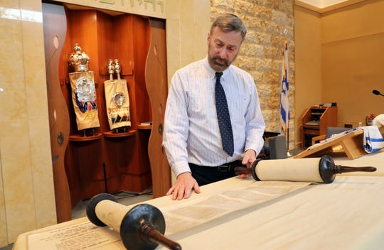 Rabbi Daniel Pernick looks at the Holocaust Torah that will be part of a memorial at Beth Am Temple in Pearl River May 1, 2019.