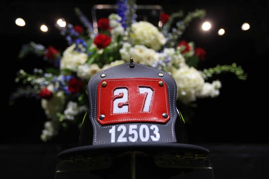 The firefighter hat of fallen Marine Staff Sgt. Christopher Slutman resta beneath the stage before a public memorial held at the University of Delaware's Bob Carpenter Center on Wednesday.