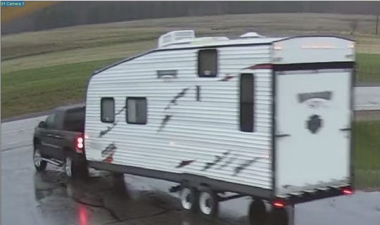 Security cameras capture a pickup pulling a stolen camper out of TJ's Auto Sales in Plover early Monday.