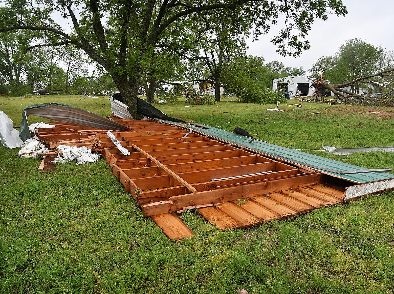 The roof of a home lies in front of heavily damaged farm buildings at Jetton Farms following Tuesday evening's tornado in Charlie, Texas.