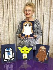 """Pat Aulds of Pat's Tea Shoppe with four paintings that guests will paint at the Star Wars Day Party she is hosting from 10 to 11 a.m. or so Saturday. There are Star Wars events around town Saturday May 4. """"May the force (forth) be with you."""""""