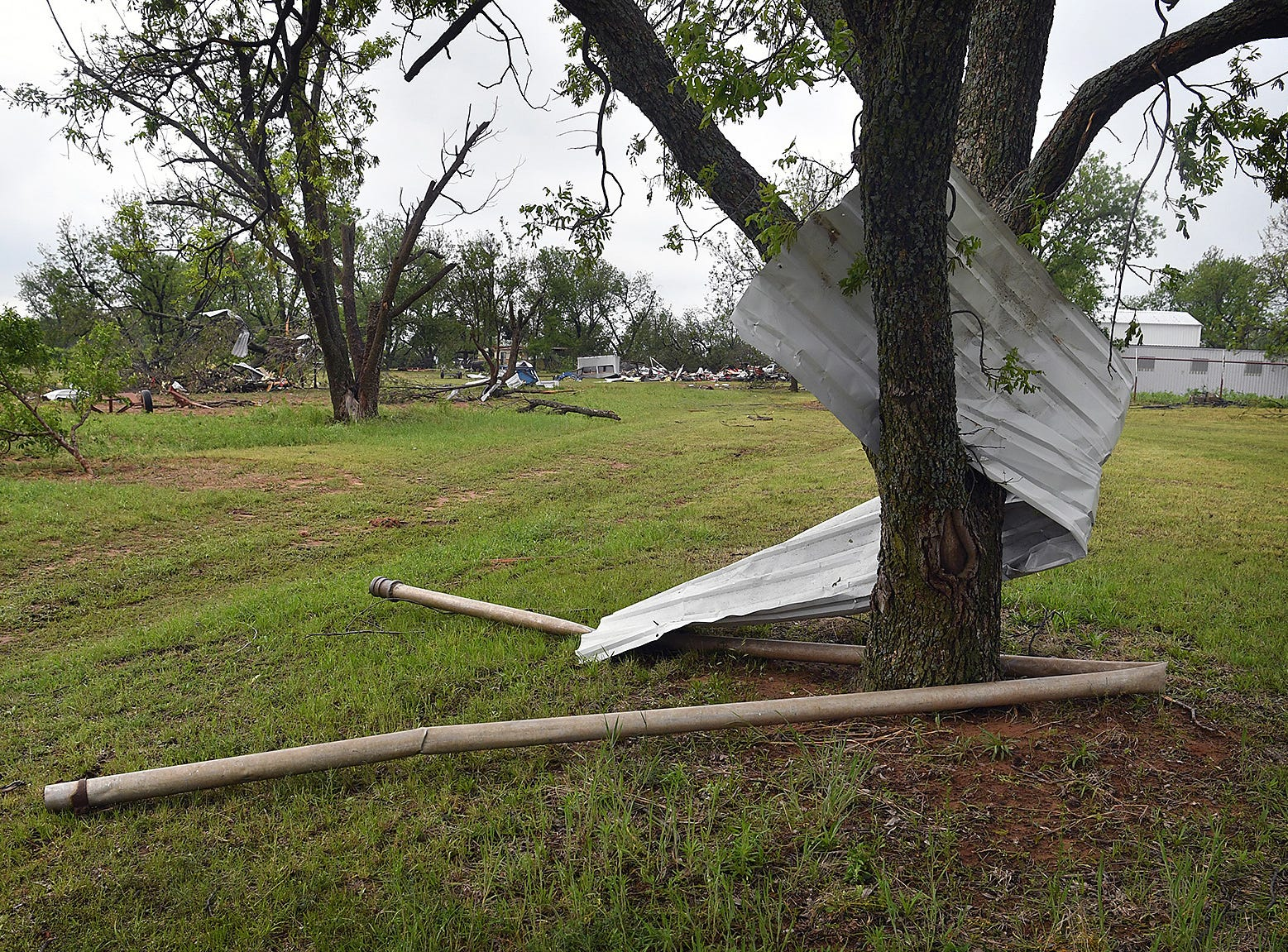 Debris from farm buildings destroyed by a tornado at Jetton Farms are lodged in trees all over the property in Charlie, Texas.