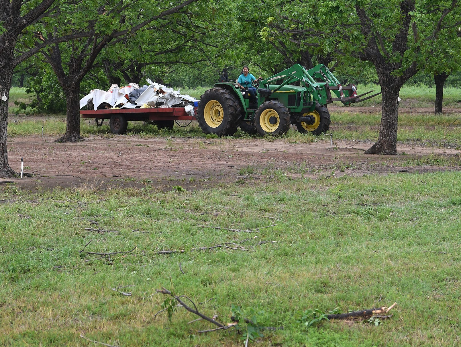 A farm worker at Montz Home Orchard in Charlie, Texas drives a tractor hauling storm debris from a tornado that struck Tuesday evening.