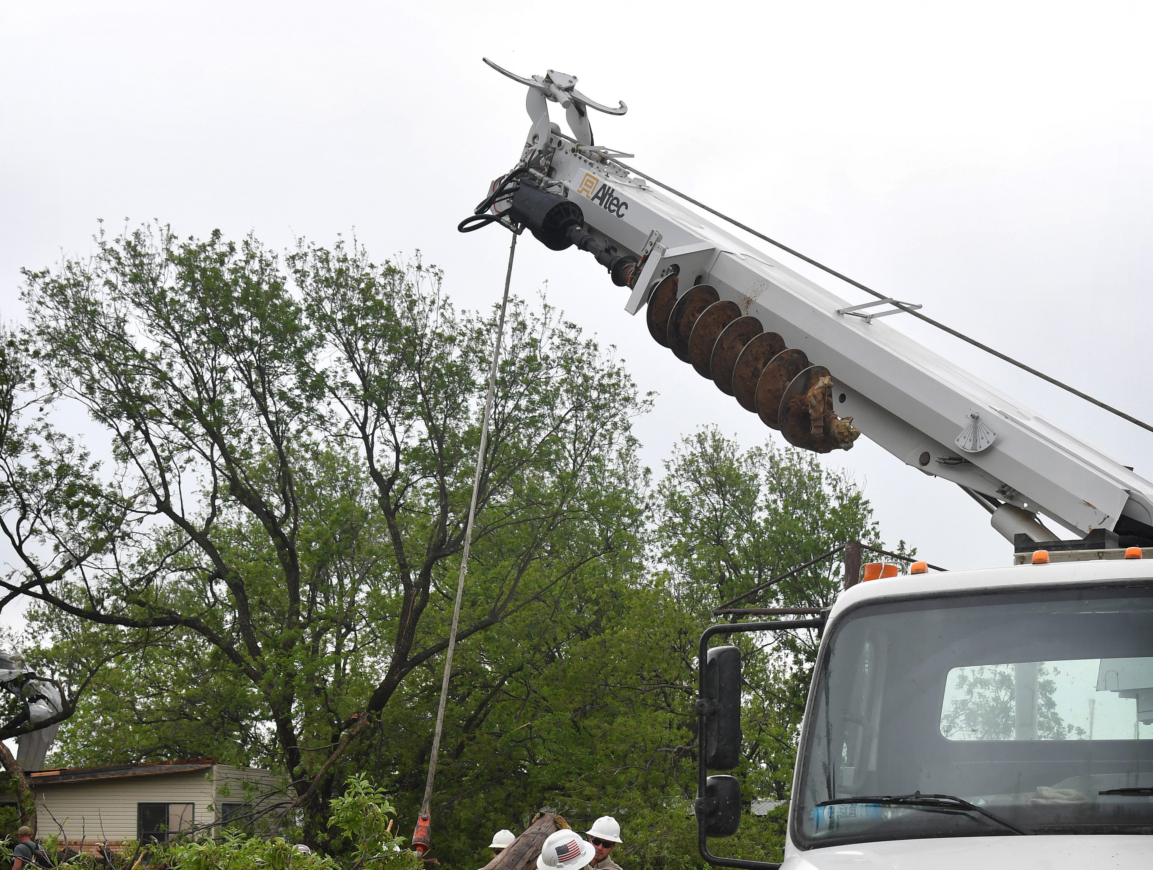 A crew from JAC Electric removes a downed power pole in Charlie where a tornado caused heavy damage at Jetton Farms.