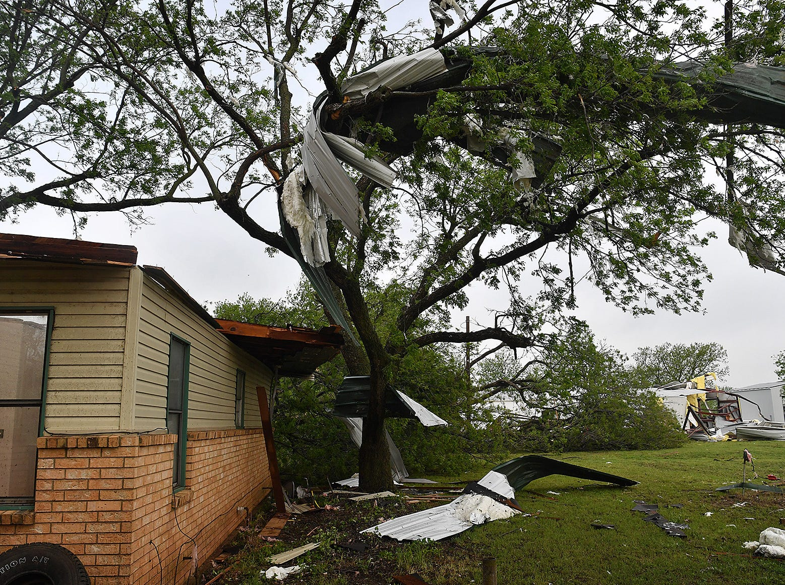 Part of the roof of a home is lodged in a tree at Jetton Farms in Charlie following a tornado Tuesday evening.