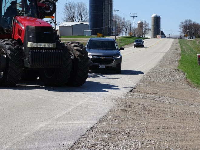 During this demonstration, Keith Oudenhoven slams on the brakes of his tractor to avoid colliding with a motorist attempting to pass him who failed to notice the tractor driver signaling to make a left turn into a farm driveway.