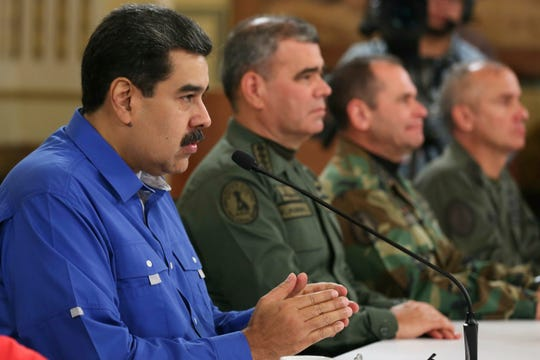 In this photo released by the Miraflores Press Office, Venezuela's President Nicolas Maduro, left, flanked by Venezuela's Defense Minister Gen. Vladimir Padrino Lopez, second left, Commander of Strategic Operations Adm. Remigio Ceballos, third from left, and Venezuela's Army Gen. Jose Ornelas, right, speaks during a televised national message at Miraflores Presidential Palace in Caracas, Venezuela, Tuesday, April 30, 2019. Opposition leader Juan Guaidó and jailed opposition leader Leopoldo Lopez took to the streets with a small contingent of armed troops early Tuesday in a call for the military to rise up and oust President Maduro. (Miraflores Press Office via AP)