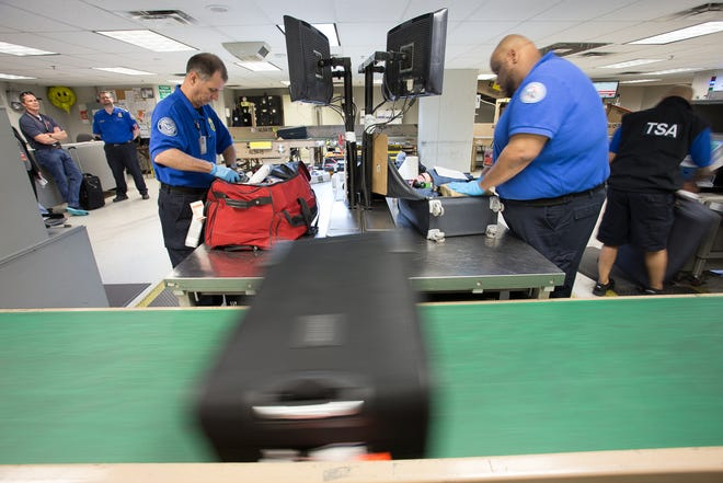 TSA agents inspect checked bags that have been flagged by security systems at Dallas-Fort Worth International Airport in April 2019.