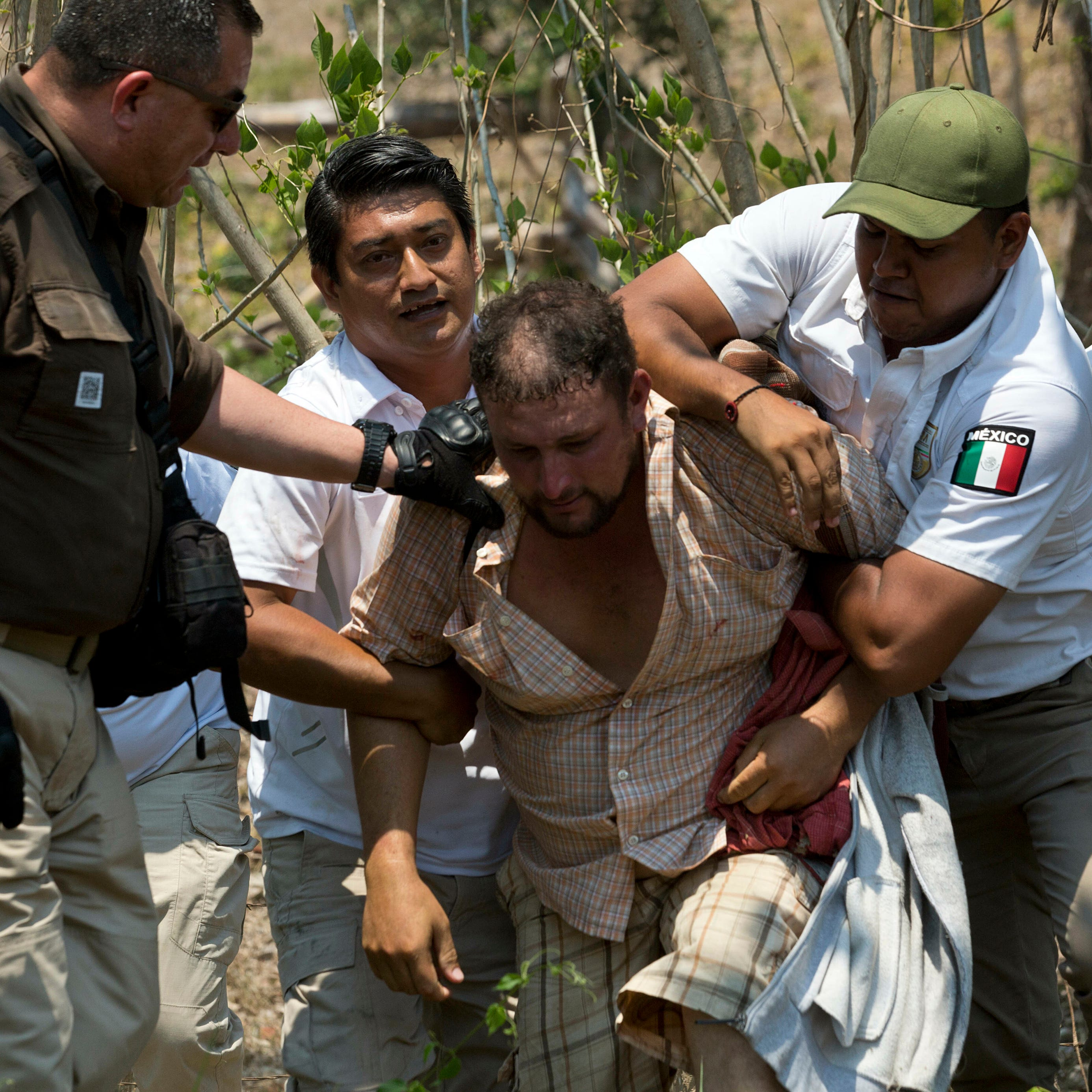 A Central American migrant is detained by Mexican immigration agents on the highway to Pijijiapan, Mexico, on April 22, 2019. Mexican police and immigration agents detained hundreds of Central American migrants Monday in the largest single raid on a migrant caravan since the groups started moving through Mexico last year.