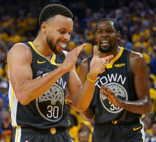 Stephen Curry and Kevin Durant celebrate during Game 2 against the Rockets.