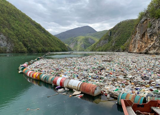 In this photo taken on April 23, 2019, plastic bottles and other garbage float in the river Drina near Visegrad, eastern Bosnia-Herzegovina. Plastic bottles, rusty barrels and even old washing machines are among tons of garbage clogging rivers in Bosnia that were once famous for their emerald color and crystal clear waters adored by rafters and adventurers as well as fishermen.