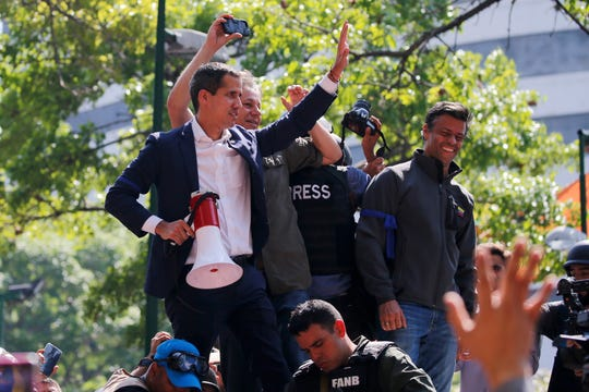 Venezuela's self-proclaimed president Juan Guaido, holding megaphone, and opposition leader Leopoldo Lopez, top right, stand before supporters in Altamira Plaza in Caracas, Venezuela, Tuesday, April 30, 2019. Guaidó and Lopez took to the streets with a small contingent of heavily armed troops early Tuesday in a bold and risky call for the military to rise up and oust President Nicolas Maduro. (AP Photo/Fernando Llano)