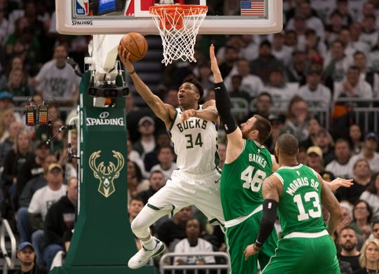 Giannis Antetokounmpo (34) drives for a reverse layup agianst the Celtics' Aron Baynes (46) during Game 2.