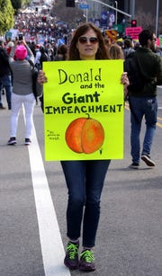 A protester holds a sign that reads 'Donald and the Giant Impeachment' at the Woman's March in Los Angeles on January 21, 2017.