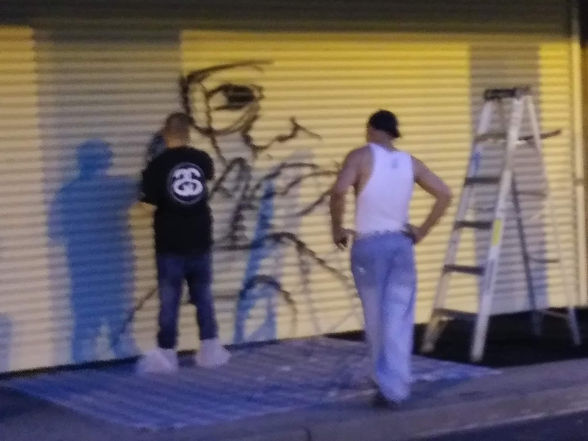 "Artists work on a mural of Earl ""Everlasting"" Sanders outside his barber shop in Asbury Park."