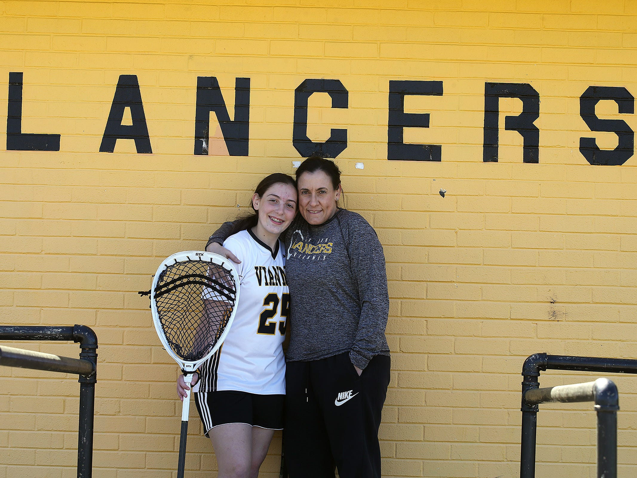 Teresa DiMezza, who is on a leave of absence from coaching the St. John Vianney girls lacrosse team, due to having a stroke late last year, hugs her daughter, Maddie, who is the goalie for the team, before a game against Neptune at St. John Vianney High School in Holmdel, NJ Wednesday, April 24, 2019.