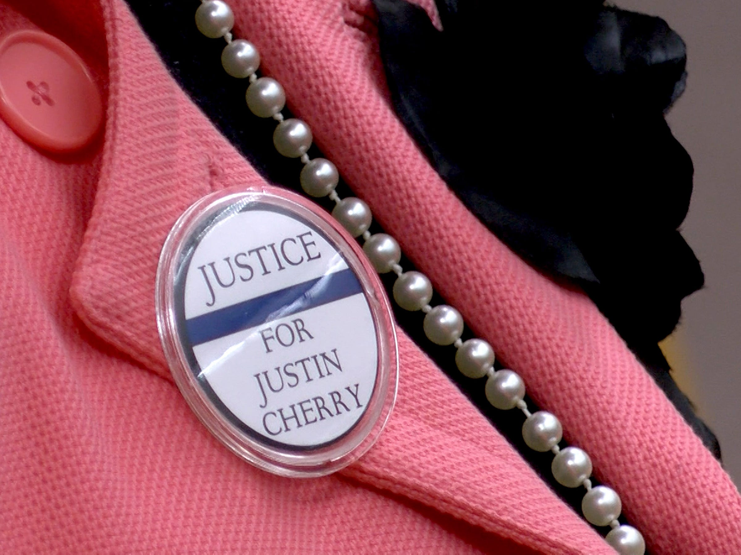 """A woman wears a """"Justice for Justin Cherry"""" pin during his trial in State Superior Court in Toms River Tuesday, April 30, 2019.  Cherry, a Tuckerton police corporal, is charged with misconduct for siccing his police dog on motorist Wendy Tucker."""