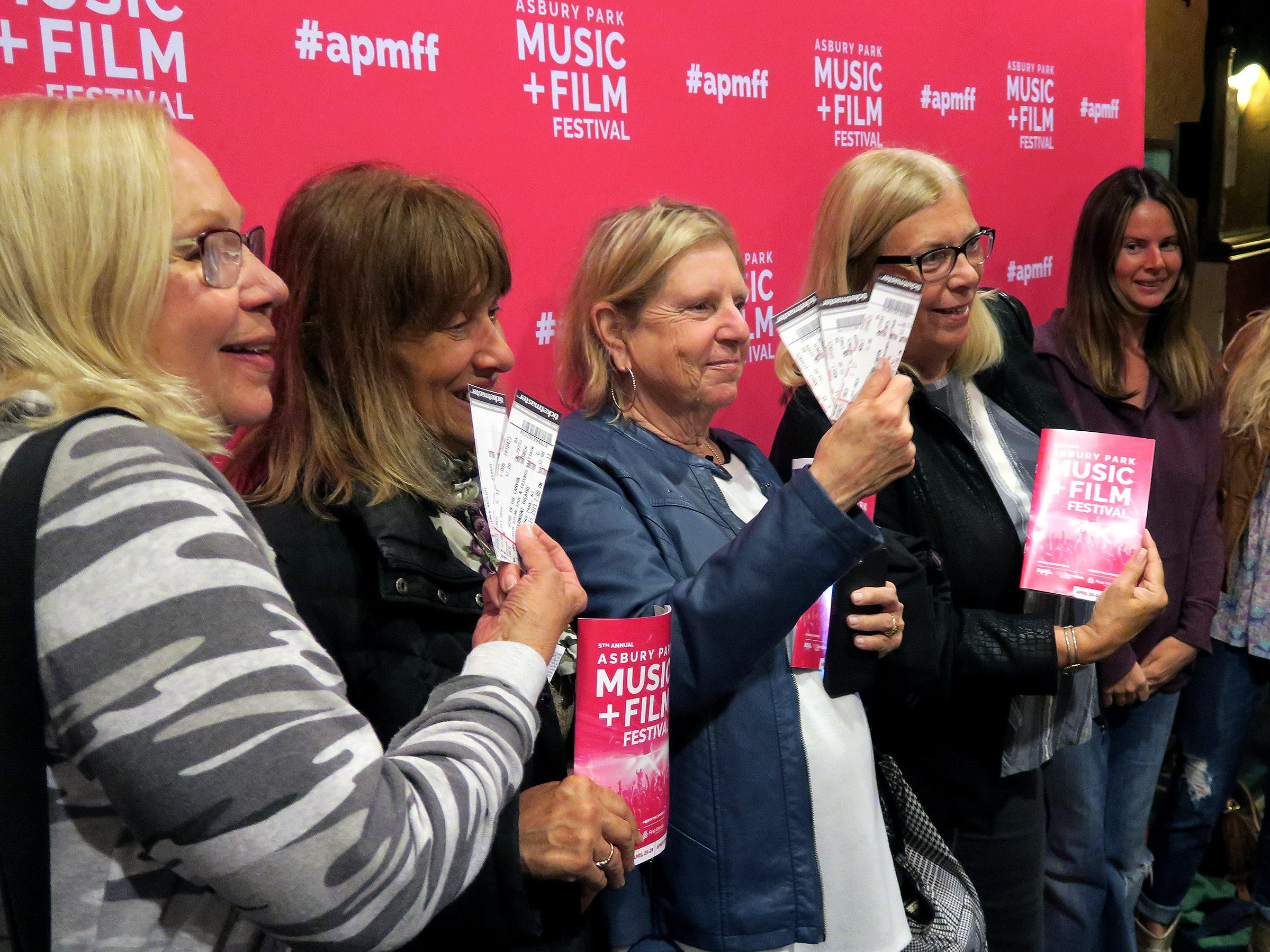 """Women display their tickets and programs as they arrive at the Paramount Theatre Thursday night, April 25, 2019, for a screening of the film """"Echo In The Canyon""""  on the opening night of the Asbury Park Music + Film Festival."""